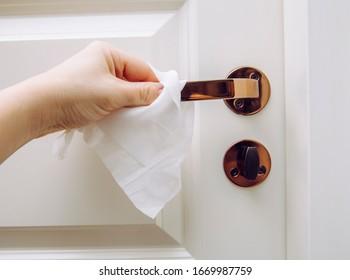 Close up view of woman hand using antibacterial wet wipe for disinfecting home room door link. - Shutterstock ID 1669987759