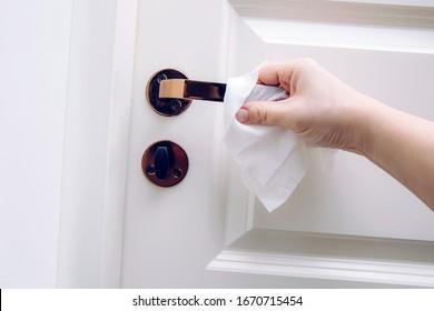 Close up view of woman hand using antibacterial wet wipe for disinfecting home room door link.
