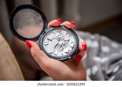 Close up view of woman hands holding broken make up powder in round shape container, red colored nails
