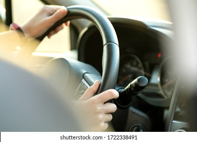 Close up view of woman hands holding steering wheel driving a car on city street on sunny day.