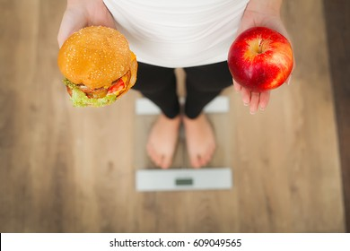 Close up view of woman making choice between apple and hamburger with blurred sides on background. Dieting concept