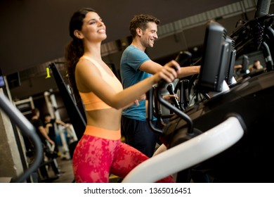 Close up view at woman and man on elliptical stepper trainer exercising in gym