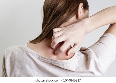 Close up view of woman scratching her neck.