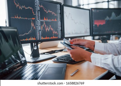 Close up view of woman's hands that holds money near the monitors with graphs.