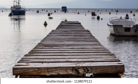 Close up view of wooden br4own bridge in a small port with few boats and buoy float on the sea.Summer in Zurkovo, Rijeka,Croatia.