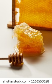 close up view of wooden honey deeper and stack of beeswax on white tabletop