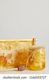 close up view of wooden honey deeper, glass jar with honey and stack of beeswax on white tabletop on grey background
