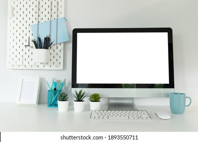 Close up view of workplace with computer, camera on white table.
