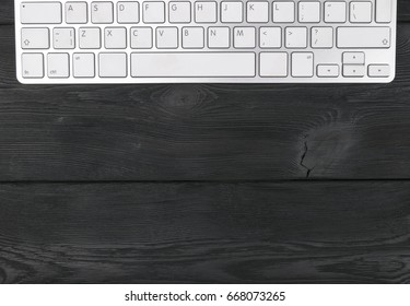 Close up view of a workplace with wireless computer keyboard, keys on old black wooden table background