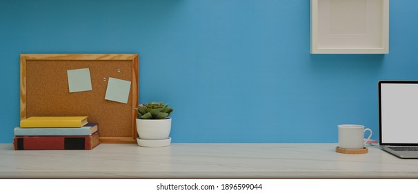 Close up view of worktable with books, laptop, notice board, decoration and copy space