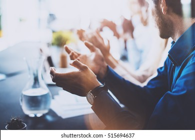 Close up view of young business partners applauding to reporter after listening speech at seminar. Professional education, work meeting, presentation or coaching concept.Horizontal,blurred background