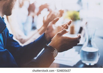 Close up view of young business partners applauding to reporter after listening report at seminar. Professional education, work meeting, presentation or coaching concept.Horizontal,blurred background