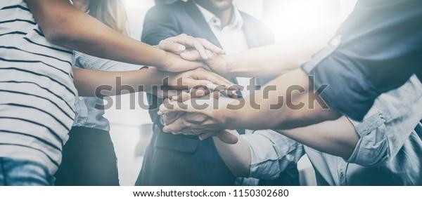 Nahaufnahme von jungen Geschäftsleuten, die ihre Hände zusammenlegen. Handstapel. Konzept der Einheit und Teamarbeit.
