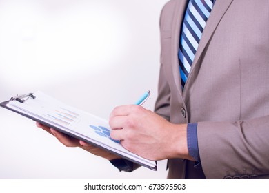 Close up view of a young businessman holding his clip board with charts isolated on white background. Writing progres down on a paper. Close-up of man's hand writing on a white paper.