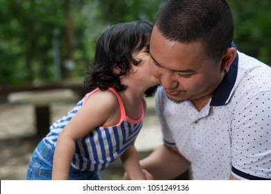 Close up view of a young daughter kissing the father. Outdoor shot with blurred trees at the background.