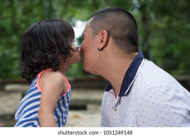 Close up view of a young daughter kissing his father. Outdoor location with forest trees at the background.