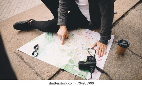 Close view of a young hipster that likes to travel. He decided to have some rest and sit down on the steps on the street. His coffee is getting colder while the guy is studing the map of the city
