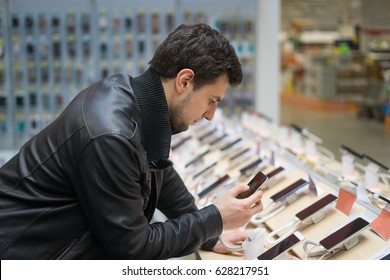 Close up view of young male customer choosing smartphone in the mobile phone shop