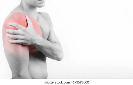 Close up view of a young man holding his shoulder in pain, isolated on white background. Shoulder and chest pain. Young man touching his shoulder for the pain. Red inflammation effect.