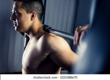 Close up view of young muscular man training hard in gym