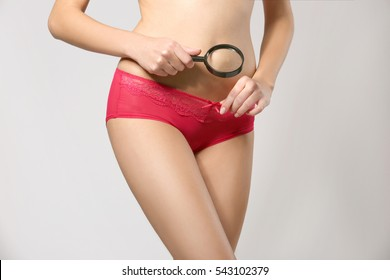 Close up view of young woman with magnifier on grey background. Gynecology concept