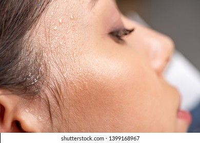 close up view of young woman with sweaty face suffering from heat on grey