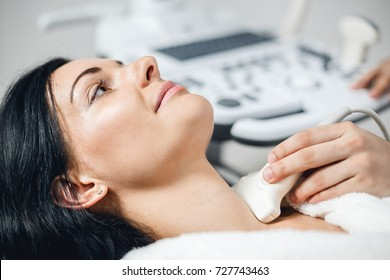 Close up view of young woman undergoing ultrasound scan in modern clinic. Beautiful woman doing neck ultrasound examination at hospital.