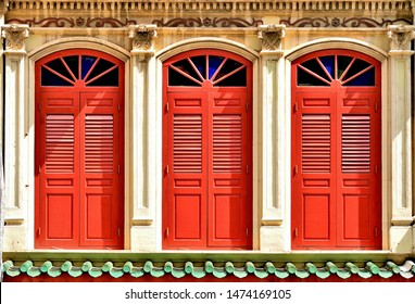 Close up of vintage arched windows with antique red wooden shutters on white exterior of traditional Singapore Peranakan or Straits Chinese shophouse in Chinatown