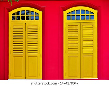 Close up of vintage arched windows with antique yellow wooden shutters on red exterior wall of traditional Singapore shophouse in historic Chinatown