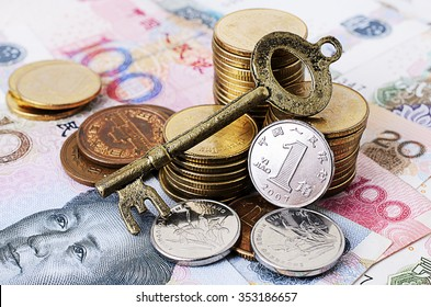 Close up of Vintage key with coins stack and china banknote