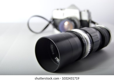 Close up of a vintage lens with blurred focus of camera in the background