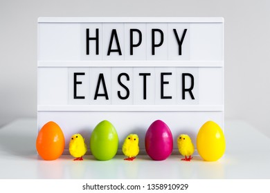 close up of vintage lightbox with happy Easter greetings, colorful eggs and decorative chicks on the table