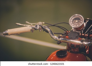 Close up of a vintage motorcycle handlebars and speedometer.