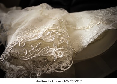 Close up vintage shot of long Wedding dress laid onbede angled from below while bride is getting ready