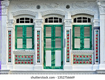 Close up of vintage windows with antique wooden shutters on green and white exterior of traditional Singapore Peranakan shophouse in historic Joo Chiat, Singapore