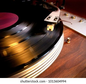 Close up of a vinyl record LP spinning on a turntable with arm and needle - vintage retro nostalgia