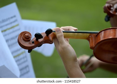 Close up of violin with music score in background.