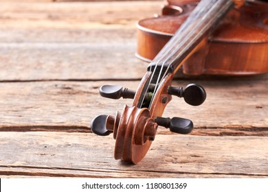 Close up violin on old wooden surface. Detail of musical instrument viola. Cello close up of scroll and peg box. Orchestral musical instrument.