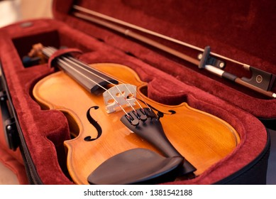 Close up of violin shallow deep of fieldViolin and bow in dark red case. Close up view of violin strings and bridge