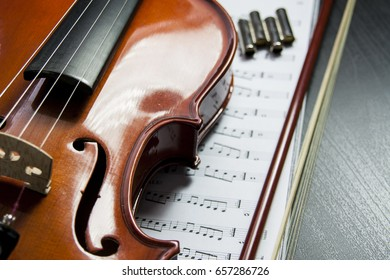 Close up of a violin, tuner and music book on a wooden table