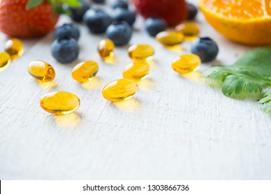 Close up vitamin supplement with healthy fruits blueberry, strawberry, and orange on white wood background.
