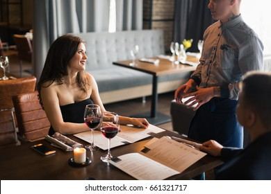 Close up of waiter hand noting down menu on tablet. Young woman ordering for food to a waiter at restaurant. Young beautiful woman thinking of food to order in front of a waiter holding tablet.