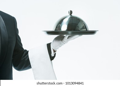 Close up waiter hand with tray and metal cloche lid cover. the concept of the best service and suggestions