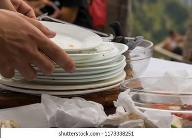 Close up of waiter hands cleaning the table from dirty dishes