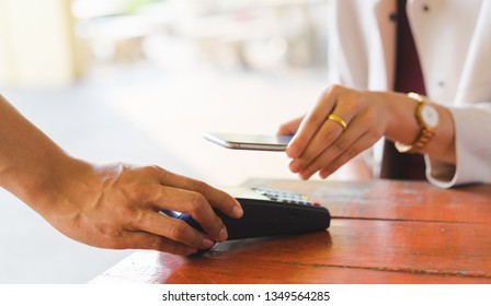 close up waiter man hand send payment machine to customer using mobile phone for paying bill by  at table in the cafe , contactless payment concept