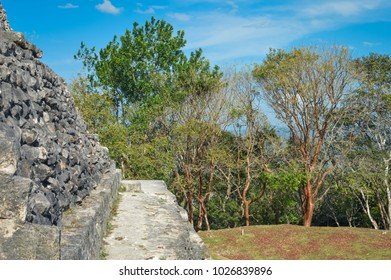 Close up of the walls of El Castillo pyramid at Xunantunich archaeological site of Mayan civilization in Western Belize. With trees and blue sky background. Central America