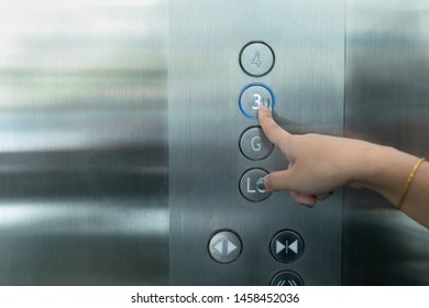 Close up waman hand press a up button of elevator.