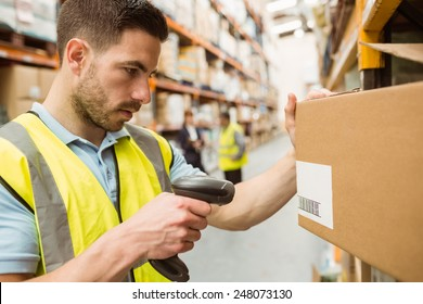 Close up of warehouse worker scanning barcodes on boxes in a large warehouse