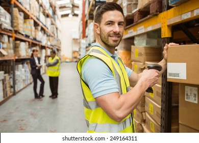 Close up of warehouse worker scanning box while smiling at camera in a large warehouse