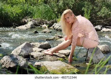 Close up warm portrait of beautiful ginger, Ophelia style woman with natural skin, wearing pink dress takes sunbaths on pond.